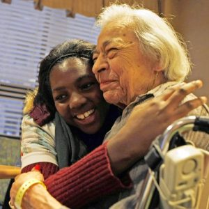 A person with dementia and a student embrace